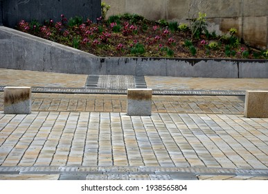 traffic barrier against the entry of cars or traffic control by means of stone blocks in the square. transport solution in the historic city center with cobblestone paving and perennial flower bed
