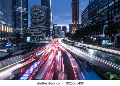 Traffic captured with blurred motion rushing along the main avenue in Jakarta business district at night in Indonesia capital city