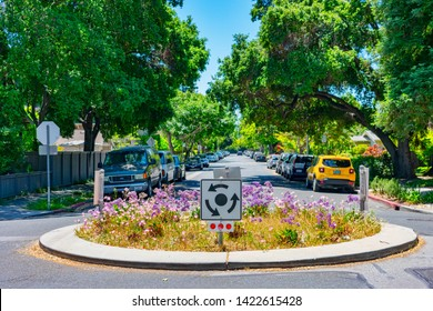 Traffic circle with landscaping and stop sign. Physical traffic calming measure for speeds, volume and cut-through traffic - Palo Alto, California, USA - June 11, 2019