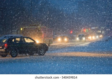 Traffic in the city in evening during heavy snowfall  picture with shallow depth of field.