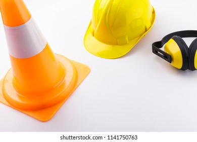 Traffic cone, hard hat, and earmuffs on a white background with copy space