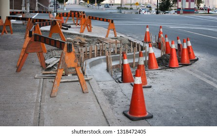 Traffic cones and barriers surrounding street construction site.
