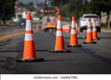 Traffic cones on road with electronic arrow pointing to the right to divert traffic and white car in distance