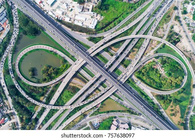 Traffic cross road junction day view from above with green tree circle road