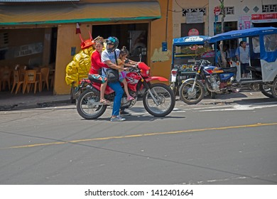 Traffic and family traffic on the street in Iquitos, Amazonia, Peru. Iquitos, Peru  7.sept.2015