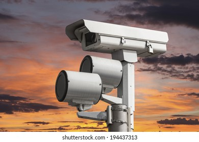 Traffic intersection signal surveillance camera with sunset sky.