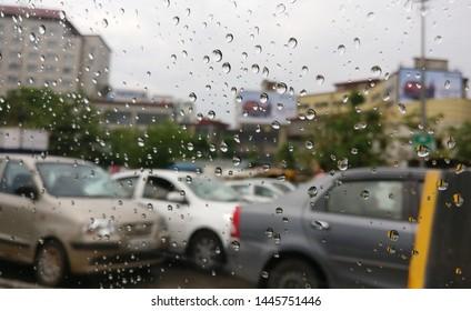 Traffic jam of cars as seen from a car glass window having rain water drops visible on it in New Delhi, India. Monsoon heavy rains strikes major cities like Mumbai, Delhi, Jaipur, Lucknow, Gurgaon