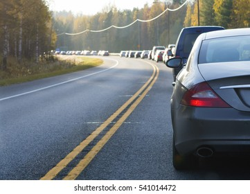 Traffic jam on an asphalt road. Curve ahead. Focus point on the car in front.
