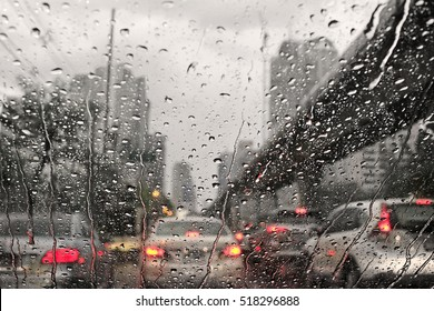 Traffic jam in rainy day with raindrops on car glasses.