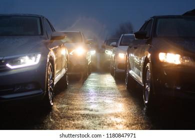 Traffic jam in the rainy night. Row of cars