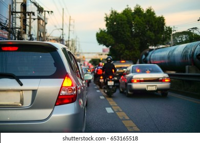 Traffic jams in the city with row of cars and motorcycles on the road at evening and bokeh lights in BANGKOK,THAILAND (with selective focus)