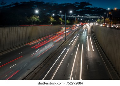 Traffic leaves London under the dusk sky on the A40 highway during evening rush hour, leaving traffic light trails