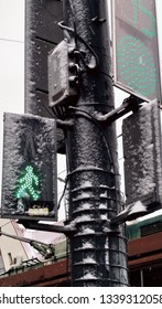 traffic light is green, allowing pedestrians to go, it is winter outside
