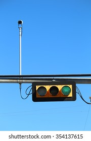 Traffic light green with enforcement camera pointed directly at the observer