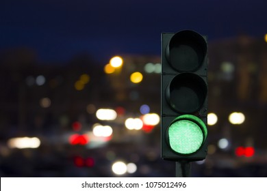 traffic light green signal on the night on the back lights of cars. Night road.