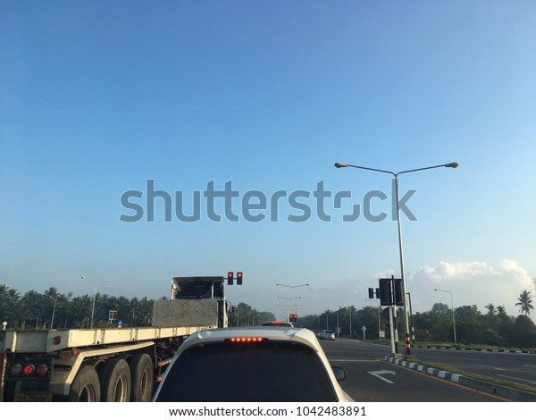 Traffic light at intersection with vehicle on road with blue sky background