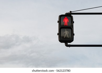 Traffic light with red light against the cloudy sky.