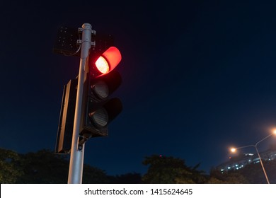 Traffic light show red light to tell other cars to stop with some trees on the background.