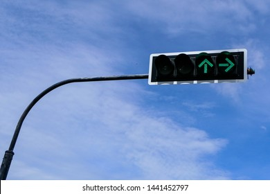 Traffic light, traffic signals, signal lights, stop lights installed on a pole in the city against a blue sky. The green light arrow, right turn and go straight on traffic signal. Safety concept.