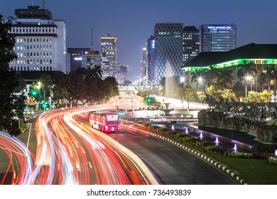 Traffic light trails along Jakarta main avenue in the business district at night in Indonesia capital city. The Transjakarta bus has its own traffic line to avoid the heavy congestion in the city.
