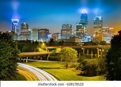 Traffic light trails in Charlotte, North Carolina. The city skyline glows on a foggy night.