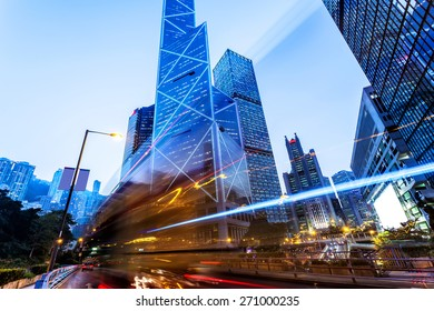 traffic light trails and office buildings in modern city at night