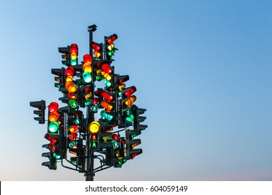 Traffic light tree with a lot of lamps under sky with a sunset.