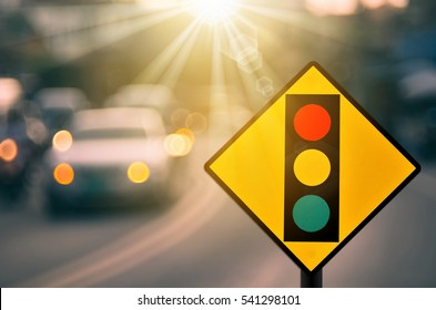 Traffic light warning sign on blur traffic road with colorful bokeh light abstract background. Copy space of transportation and travel concept. Retro tone filter color style.
