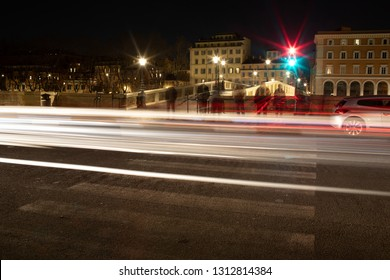 Traffic lights by night in Trastevere, Rome, Italy. Long exposure shot. Unrecognizable persons.