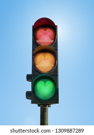 Traffic lights with glowing green, orange and red hearts against blue sky- love concept