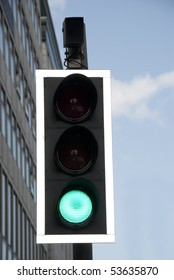 Traffic lights with green sign on street