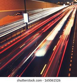 Traffic lights in motion blur on road of Dubai. City never sleeps.