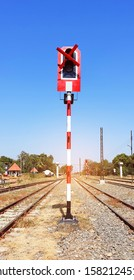 Traffic lights for train notifications.Symbol for the train to stop running.Stands predominantly midway between the railway tracks Under the bright blue sky.