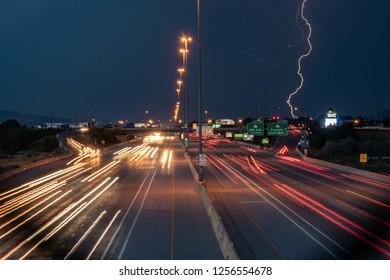 Traffic at night on freeway with lightning strike