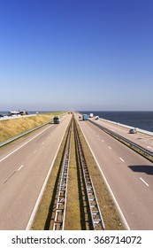 Traffic on the Afsluitdijk on a sunny day in The Netherlands. The Afsluitdijk is a dike over 32km damming off the former Zuiderzee, a salt water inlet of the North Sea.