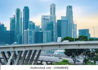 Traffic on bridge of Singapore downtown, sunset cityscape with skyscrapers