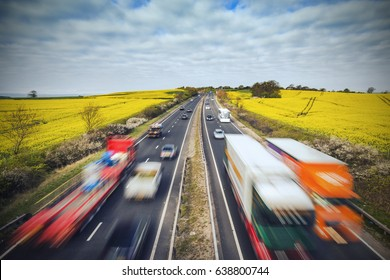 Traffic on British Motorway Among Yellow Rapeseed Fields