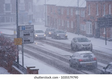 traffic on busy road in blizzard conditions in the UK with buildings in background