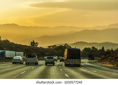 Traffic on the Interstate 60 in the Moreno Valley near Los Angeles with the San Gabriel mountains in the background, on a nice evening of summer before sunset, California.
