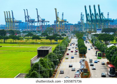Traffic on road, industrial port view with cranes on background, Singapore