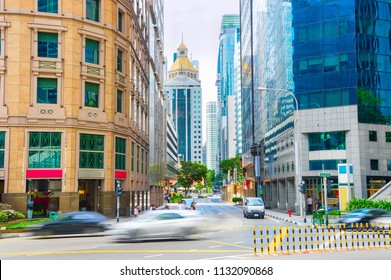 Traffic on street of Singapore business downtown district with office buildings of modern architecture
