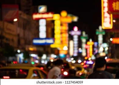 Traffic on Yaowarat Road passes below lit signs in the Chinatown district at night restaurants and street food stalls. Blur and bokeh background.