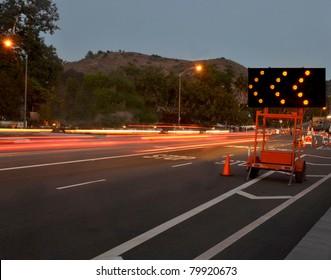 traffic passing by construction/Night Traffic Warning/Night traffic passing by a warning sign