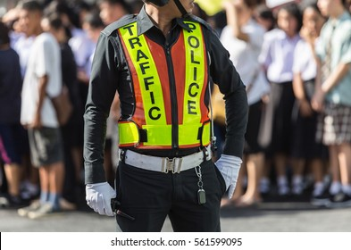Traffic police standing on the road while doing his work.