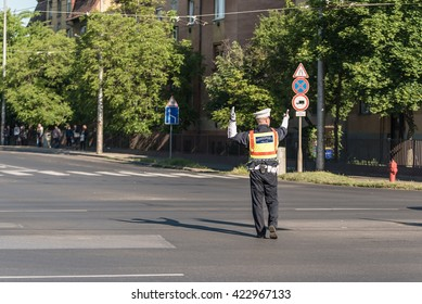 Traffic policeman directing cars in a crossing road, detail