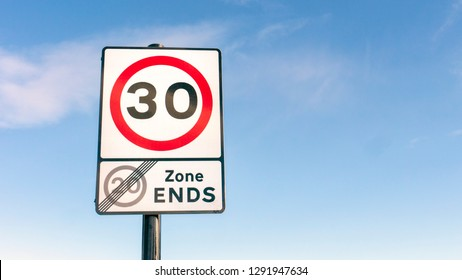 Traffic Road sign for 30mph (miles per hour) speed limit zone and end of 20 mph speed limit zone in England
