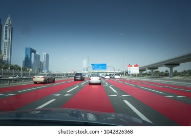 Traffic at Sheikh Zayed Road in Dubai in a summer day. Cars on the road with red lines