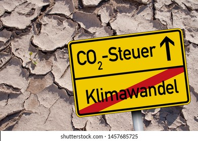 Traffic sign with CO2 Tax- Steuer and climate change - Klimawandel on dry ground