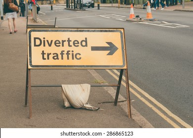Traffic Sign 'Diverted Traffic' with pedestrians crossing the road closeup