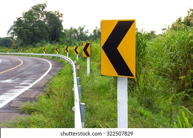Traffic sign indicating a curve to the left and straight ahead a row rural forest grass.
